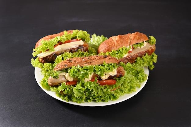 Hotdog met veel groene salade en gebakken worstjes