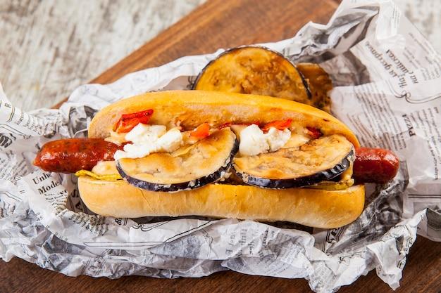 Hotdog met worst aubergine kwark tomaat en chili