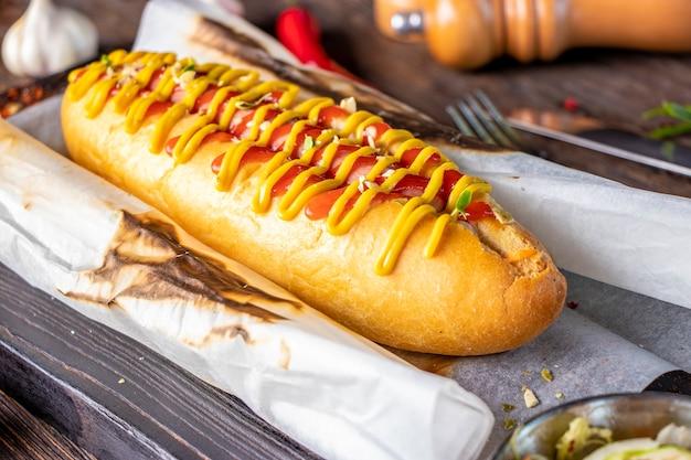 Hotdog met worst bevindt zich op een houten bord tegen een donkere achtergrond, rustieke stijl, horizontale oriëntatie, close-up