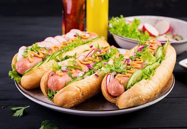 Hotdog met worst, komkommer, radijs en sla op donkere houten tafel. zomer hotdog.