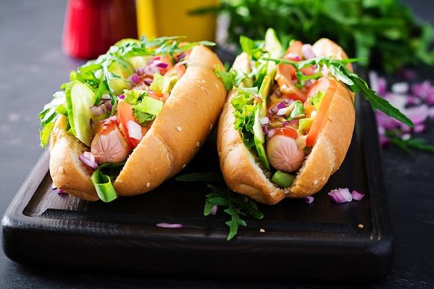 Hotdog met worst, komkommer, tomaat en rode ui op donkere tafel.