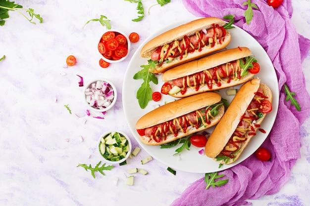 Hotdog met worst. spek, komkommer, tomaat en rode ui op witte plaat. bovenaanzicht plat leggen.