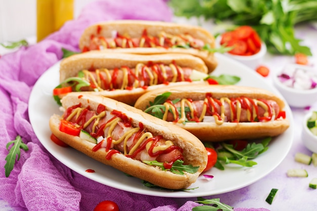Hotdog met worst. spek, komkommer, tomaat en rode ui op witte plaat