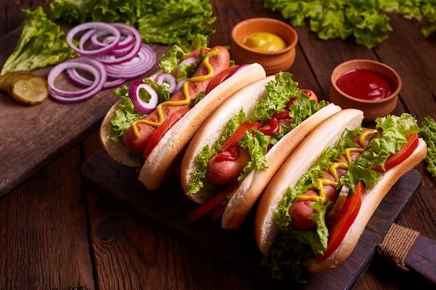 Hotdogs. gegrilde hotdogs met mosterd en ketchup op een picknick houten tafel. belegd broodje
