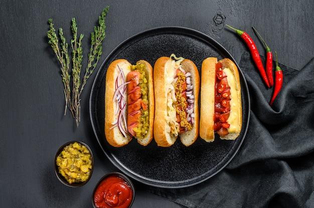 Hotdogs met diverse toppings. heerlijke hotdogs met varkens- en rundvleesworstjes. zwarte achtergrond. bovenaanzicht