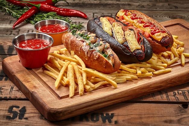 Hotdogs met frietjes en sauzen op een houten bord