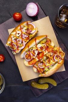 Hotdogs met groenten, mosterd en ketchup op een snijplank op een donkere achtergrond, bovenaanzicht