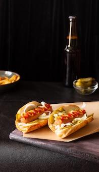 Hotdogs met groenten, mosterd en ketchup op een snijplank op een donkere achtergrond