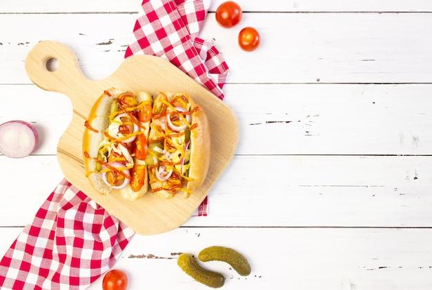 Hotdogs met groenten, mosterd en ketchup op een snijplank op een witte houten tafel, bovenaanzicht, copyspace