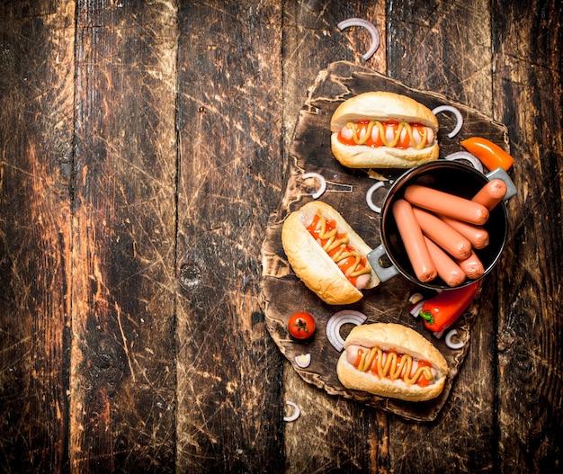 Hotdogs met mosterd, uien en tomaten op houten tafel.