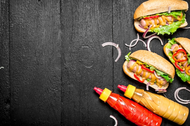 Hotdogs met uien, tomaten en hete mosterd op zwart bord.