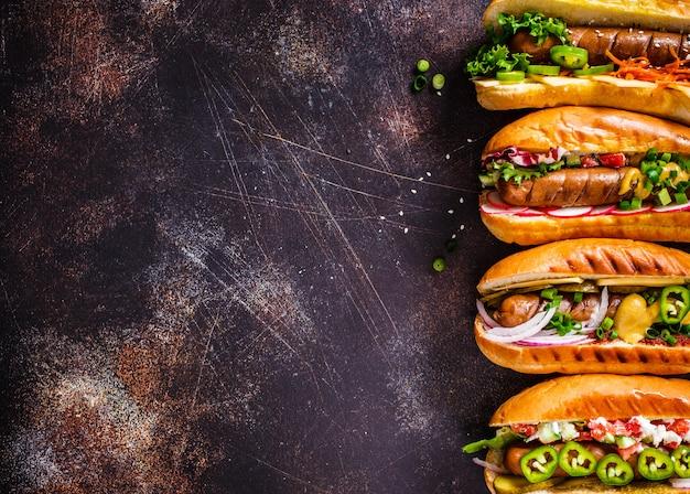 Hotdogs met verschillende toppings op donkere achtergrond, kopie ruimte, bovenaanzicht,