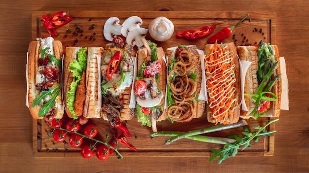 Hotdogs met verschillende toppings op een houten bord