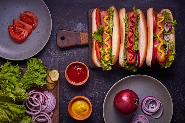 Hotdogs met worst, gebakken ui, korianderblaadjes, kaassaus en mosterd. fast food. bovenaanzicht, kopieer ruimte