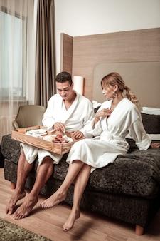 Hotel badjassen. paar dat hotelbadjassen draagt die op bed zitten en 's ochtends genieten van eten
