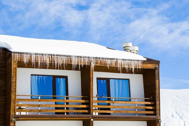Hotel buitenkant in skigebied, sneeuw, zonnige dag en ijs. ramen en dak.