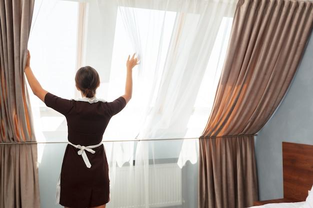 Hotel dienstverleningsconcept. kamermeisje aan te passen gordijnen in de kamer