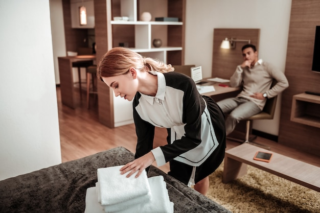 Hotel meid. prachtige hotelmeid in wit en zwart uniform die 's ochtends witte handdoeken meebrengt