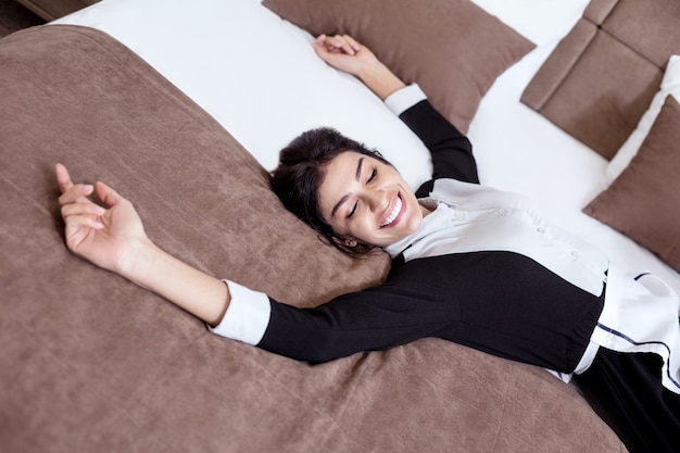 Hotel personeel. bovenaanzicht van een aantrekkelijke jonge hotelmeid liggend op het bed terwijl u in een goed humeur bent