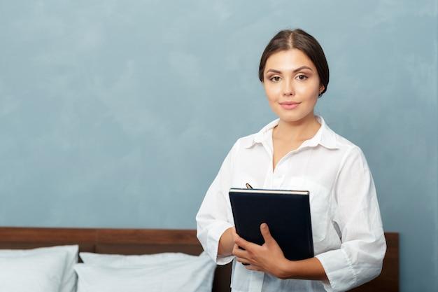 Hotelbeheerder die in klembord schrijft