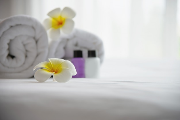 Hotelhanddoek en shampoo en zeepbadfles die op wit bed met verfraaide plumeriabloem wordt geplaatst - ontspan vakantie bij het concept van de hoteltoevlucht
