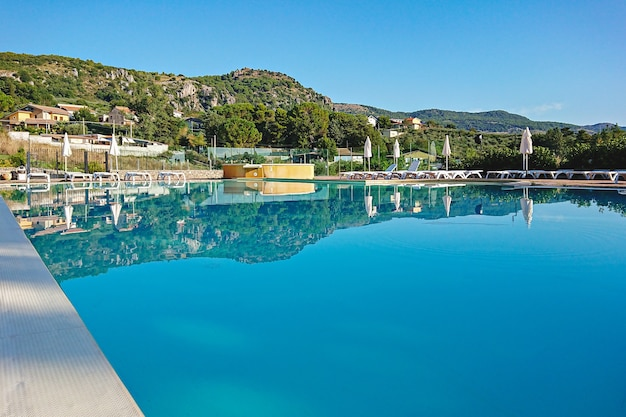 Hotelloungezone met zwembad verborgen tussen de bergen in de ochtend piana degli albanesi, italië
