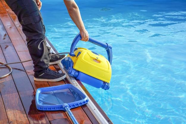 Hotelmedewerker die het zwembad schoonmaakt