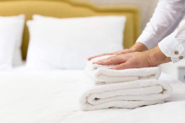 Hotelpersoneel dat kussen op bed opzet