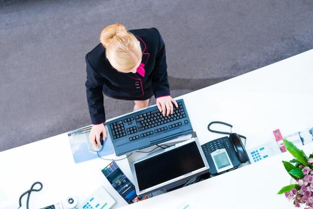Hotelreceptionist die bij voorkantoor werken