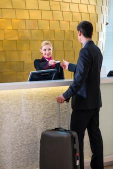 Hotelreceptionnistcontrole de mens die zeer belangrijke kaart geeft