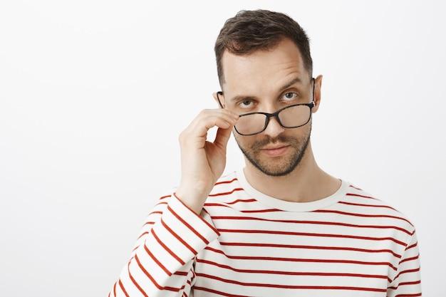 Hou je mij voor de gek. binnen schot van twijfelachtige serieuze volwassen ondernemer met borstelhaar, bril opstijgend en wenkbrauw nieuwsgierig optillen