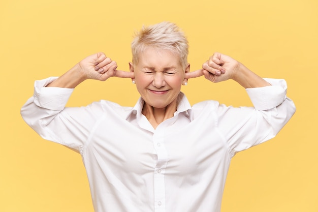 Hou je mond! geïsoleerd beeld van gefrustreerde boze volwassen vrouw met geverfd pixiehaar die de ogen gesloten houdt en de oren verstopt, kan geen harde geluiden of lawaai uitstaan, gestrest zijn tijdens ruzie of ruzie
