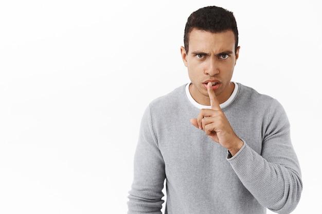 Hou je mond of anders. serieus uitziende boze jongeman die iemand uitscheldt die te luid is, zwijgt?