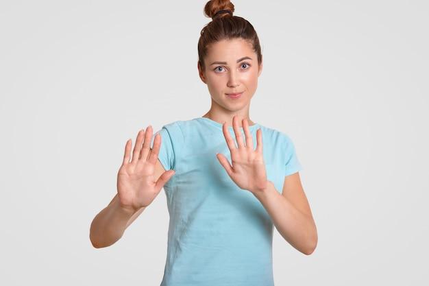 Hou op! de vrij jonge vrouw met aantrekkelijke blik, houdt palmen over borst, maakt weigeringsgebaar, gekleed in toevallige t-shirt, die over wit wordt geïsoleerd. mensen, jeugd en lichaamstaal concept