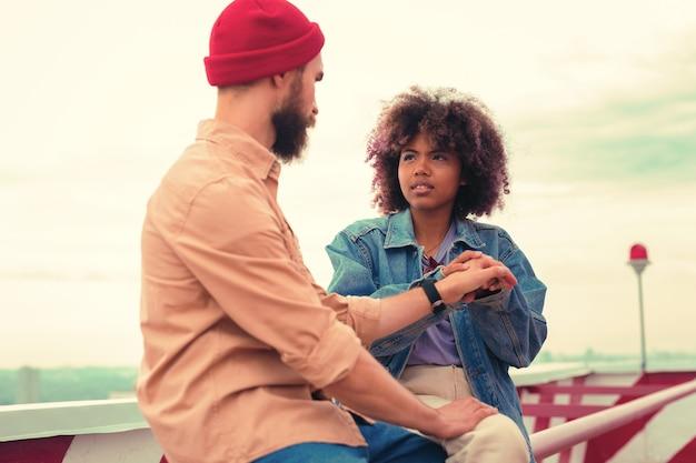 Hou op. ernstig jong meisje zit met haar vriendje en raakt zijn hand aan terwijl ze een moeilijk gesprek met hem heeft