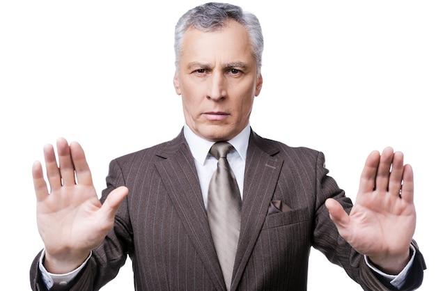 Hou op! ernstige volwassen man in formalwear die zijn handpalmen laat zien en naar de camera kijkt terwijl hij tegen een witte achtergrond staat
