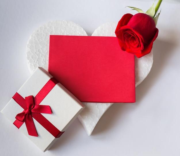 Hou van achtergrond met geschenkdoos en rode roos en rood papier met ruimte om te ontwerpen