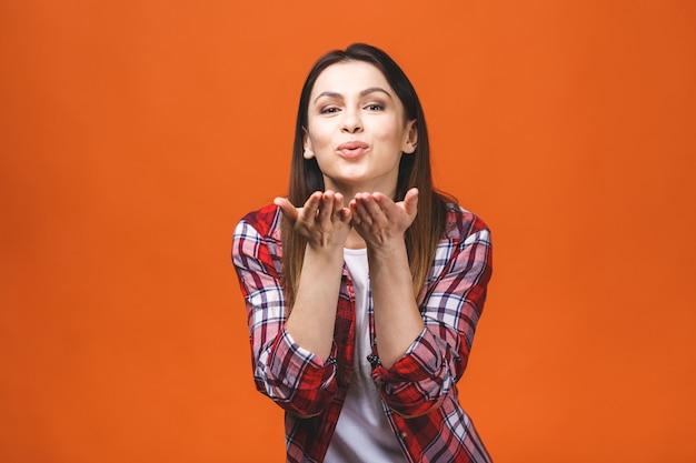 Hou van concept. portret van een jonge brunette meisje poseren blaast een kus, geïsoleerd tegen oranje achtergrond.