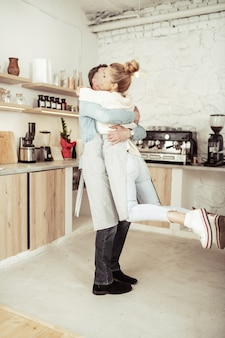 Hou van elkaar. gelukkige vrouw springen in de armen van haar knappe man in hun keuken.