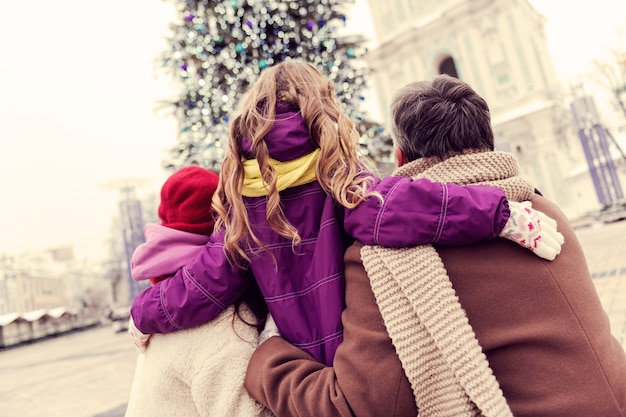 Hou van hen. schattige kleine vrouw kijkt in de ene richting met mama en papa terwijl ze geniet van de winterstad