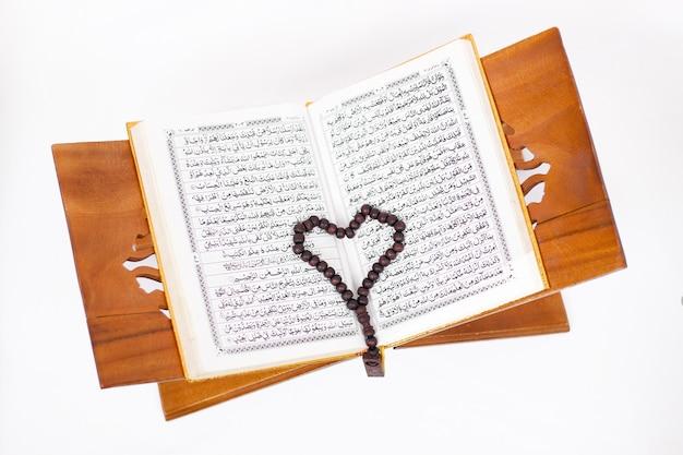Hou van het heilige boek koran en tasbih geïsoleerd op een witte achtergrond