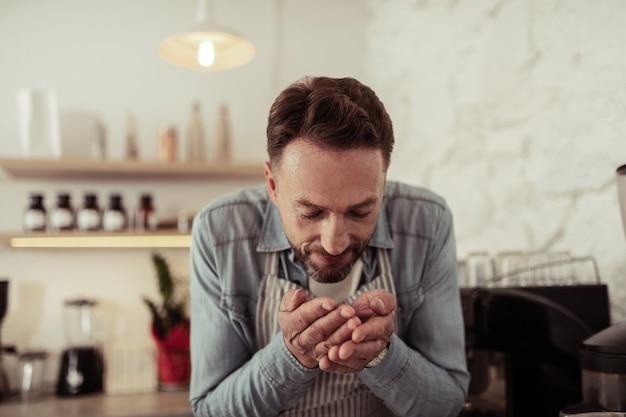 Hou van je werk. glimlachende café-eigenaar die vers gebrande koffiebonen in zijn handen ruikt.