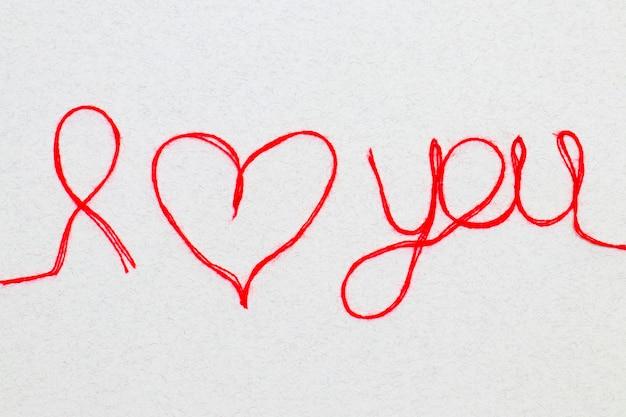Hou van je woorden en hartsymbool gemaakt van rode draad geïsoleerd voor je valentijnsdag