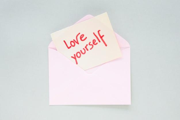 Hou van jezelf opschrift op papier in een lichte envelop