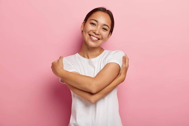 Hou van jezelf. vrij blij aziatisch meisje omhelst zichzelf, voelt troost en zorgzaamheid, kantelt het hoofd, draagt een wit t-shirt, heeft geen make-up, geïsoleerd over een roze muur, denkt aan minnaar, wil in zijn warme armen zijn