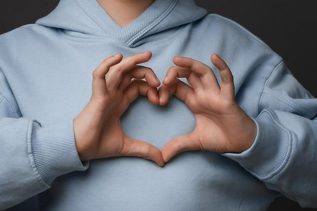 Hou van jou. bijgesneden close-up van jongen 10-12 jaar oud, gekleed in vrijetijdskleding, hartsymbool maken