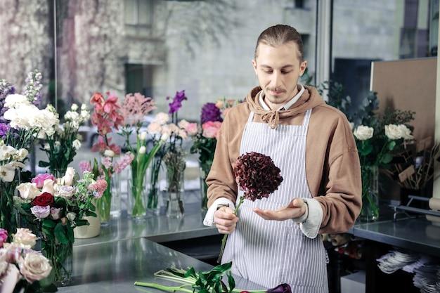 Hou van mijn werk. blije bloemist die zich op zijn werkplaats bevindt en naar bloem kijkt
