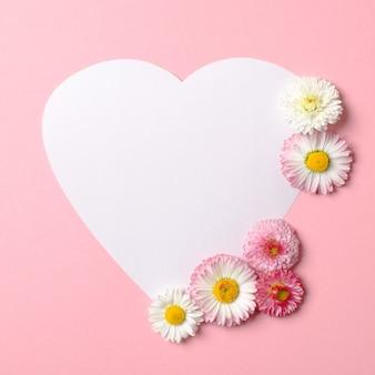 Hou van natuur concept. madeliefjebloemen en witte hartvormige papieren kaart op pastel roze achtergrond.