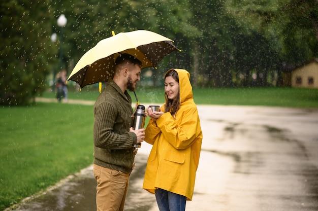 Hou van paar met hete thee in park, regenachtige zomerdag. man en vrouw staan onder paraplu in regen, romantische date op wandelpad, nat weer in steegje