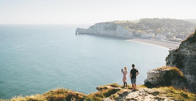 Hou van paar wandelen en het nemen van foto van de kliffen van etretat en de atlantische oceaan in etretat, frankrijk